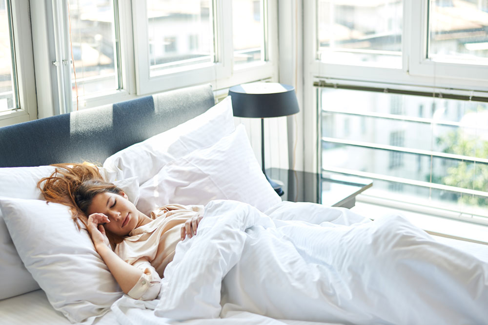 Young female in bright windowed room sleeping on her back with all white decor and one hand comfortably on her pillow