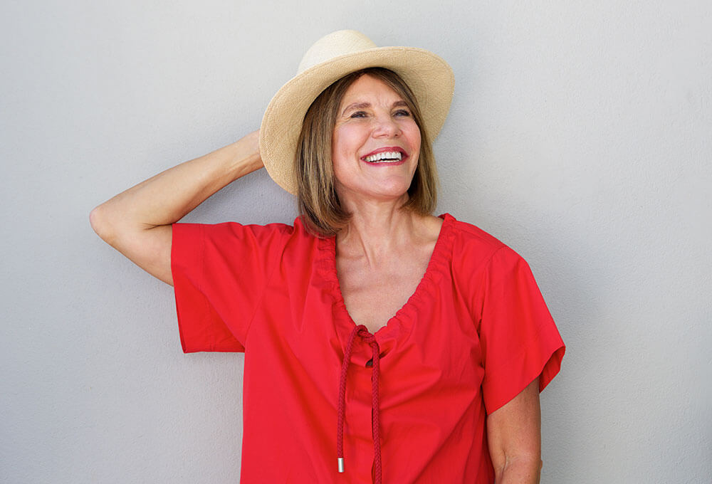 Older woman in red smiling and holding one hand on her head with a hat