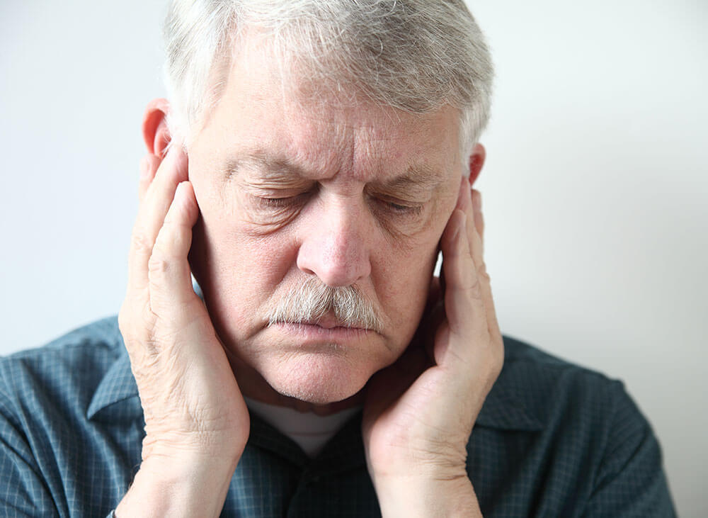 Older man holding both of his ears