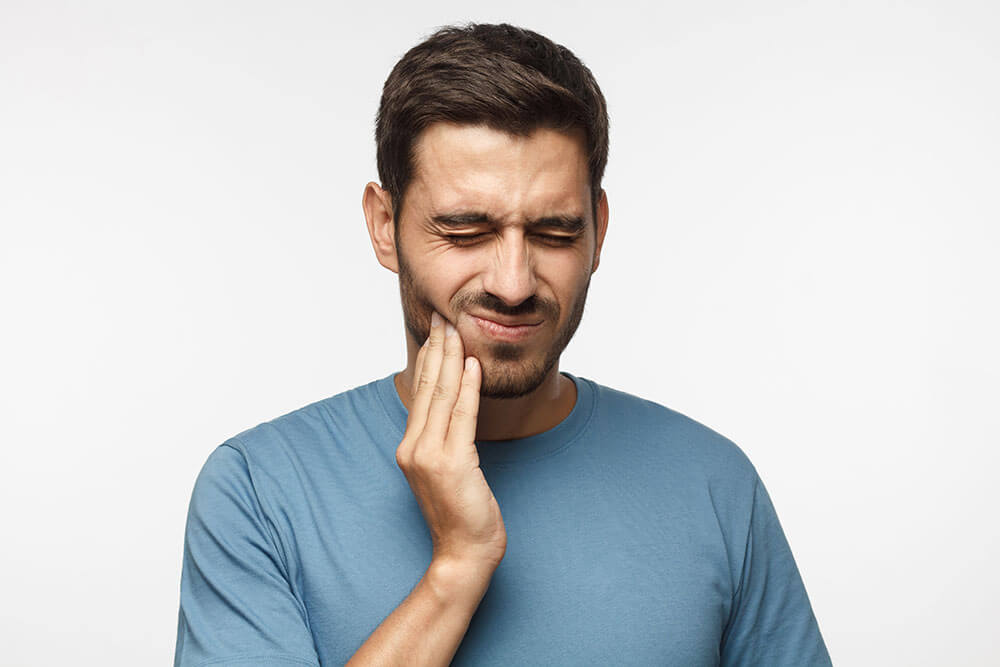 Young man holding his jaw jaw in pain