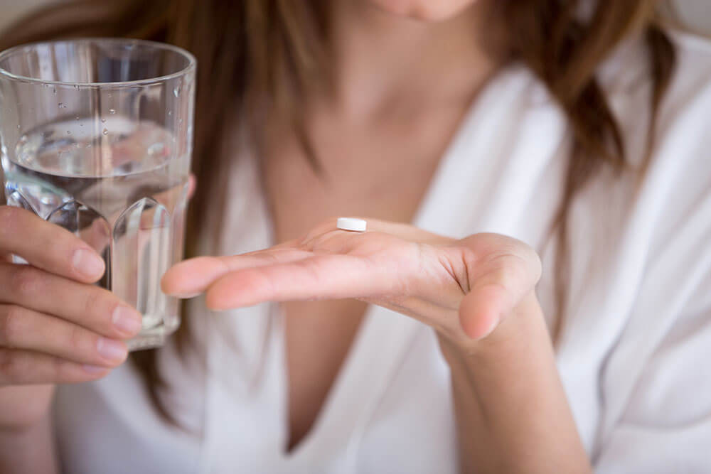Woman holding a pill for medication and a glass of water