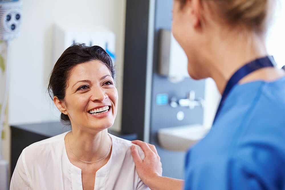 Doctor consulting a woman patient who is smiling back