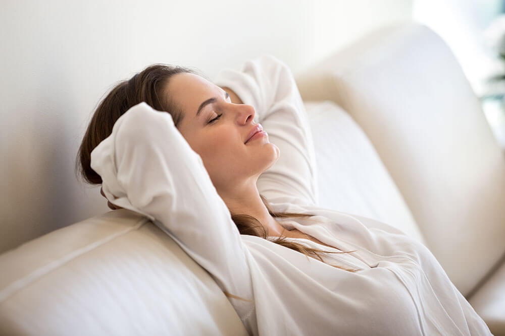Young woman resting on a couch with her eyes closed and her arms behind her head