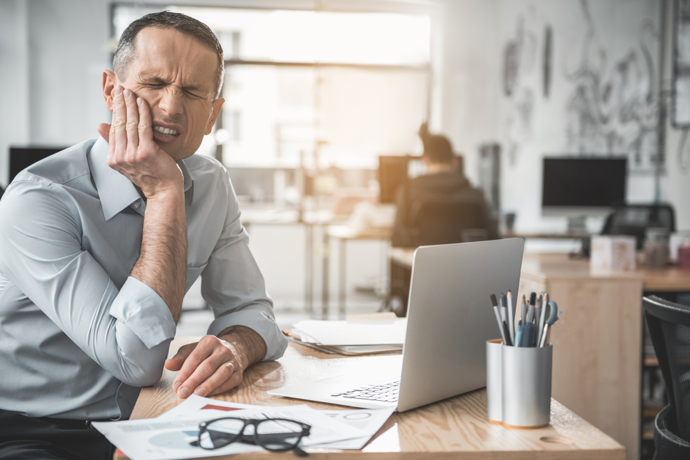 stressed out businessman with jaw pain sitting at his desk