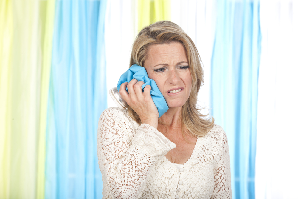 woman with jaw pain applying an ice pack to her face