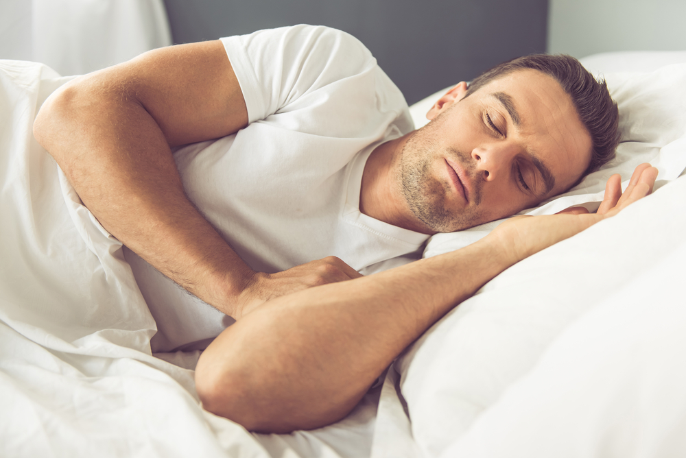 man sleeping on his side in bed